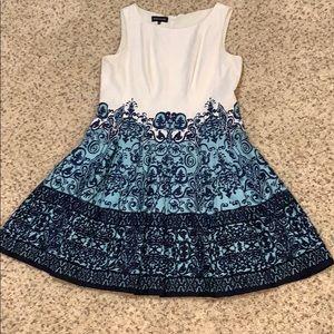 Sleeveless elegant fitted dress with full skirt.